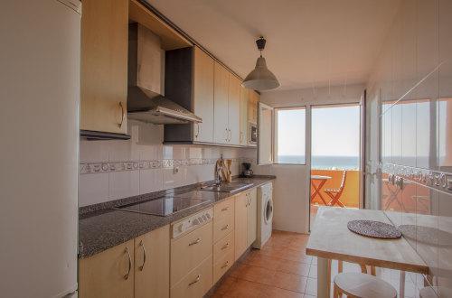 Cocina con vitrocerámica y salida a terraza