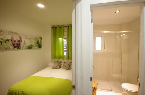 Dormitorio con cama individual y baño integrado