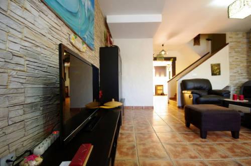 Salón con televisor y escaleras